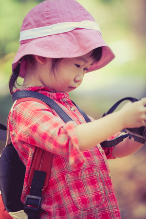 pursuing: Cute little asian girl checking and reviewing photos in professional digital camera over nature background. Active lifestyle, curiosity, pursuing a hobby, technology and kids concept. Retro style. Outdoors.