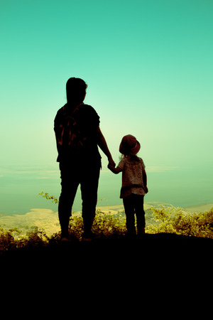 Silhouette back view of mother and daughter clasping hand together and looking at sky. Friendly family. Cross process.