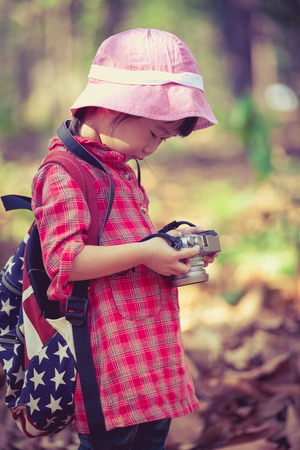 pursuing: Cute little asian girl checking and reviewing photos in professional digital camera over nature background. Active lifestyle, curiosity, pursuing a hobby, technology and kids concept. Retro style. Stock Photo
