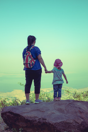 clasping: Back view of mother and daughter standing on boulder and clasping hand together. Friendly family. Cross process.
