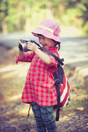 45 years old: Cute little asian girl taking photos by professional digital camera in garden background. Photo in retro style. Pretty child in nature. Outdoors portrait. Photo in retro style.