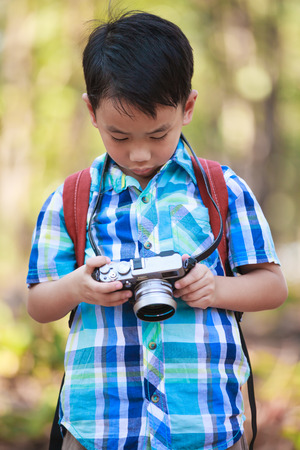 pursuing: Asian smart boy checking and reviewing photos in professional digital camera over nature background. Active lifestyle, curiosity, pursuing a hobby, technology and kids concept.
