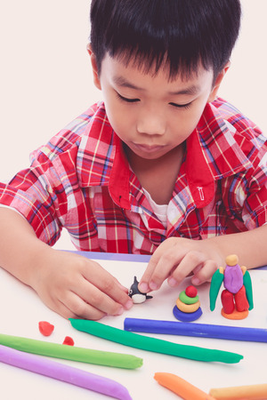 moulding: Smart asian boy playing and creating toys from play dough. Child moulding whale modeling clay. Strengthen the imagination of child Stock Photo