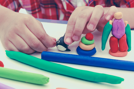 clay modeling: Close up childs hand creating toys from play dough. Strengthen the imagination of child. Child moulding whale modeling clay. Vintage picture style. Stock Photo