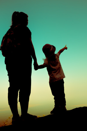 clasping: Silhouette back view of mother and daughter clasping hand together. Girl point to sky. Friendly family. Cross process. Stock Photo