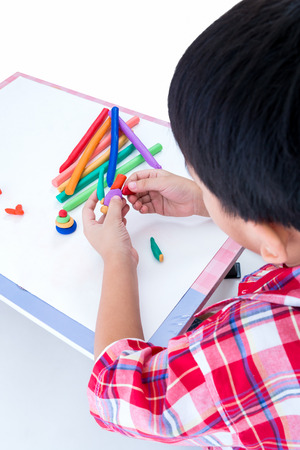 Little boy playing and creating toys from play dough, on white background. Child moulding robot modeling clay. Strengthen the imagination of child