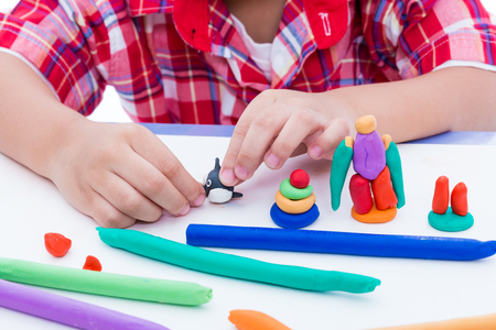 strengthen: Close up childs hand creating toys from play dough. Strengthen the imagination of child. Child moulding whale modeling clay.