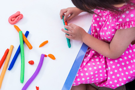 strengthen: Little girl creating toys from play dough. Child moulding modeling clay. Strengthen the imagination of child Stock Photo