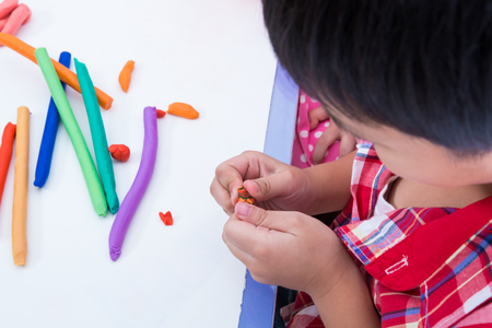 strengthen: Little boy creating toys from play dough. Child moulding modeling clay. Strengthen the imagination of child Stock Photo