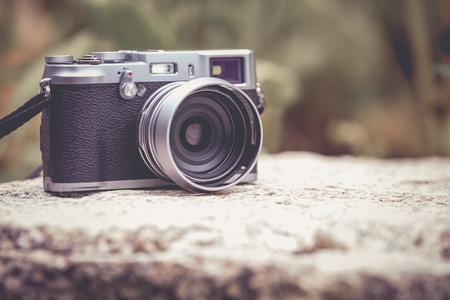 Cámara digital de estilo vintage en roca sobre fondo borroso de la naturaleza. Profundidad de campo con enfoque en la cámara. Al aire libre. Estilo de imagen retro. Foto de archivo
