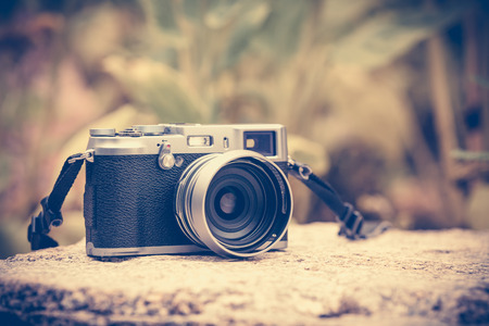 cross process: Vintage-style digital camera on boulder over blurred nature background. Shallow depth of field with focus on camera. Outdoor. Cross process picture style. Stock Photo