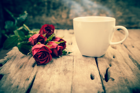 cross process: Bouquet of beautiful red roses and steaming coffee cup for Valentines Day on blurred wooden background. Vintage picture style. Cross process. Shallow depth of field (dof), selective focus.