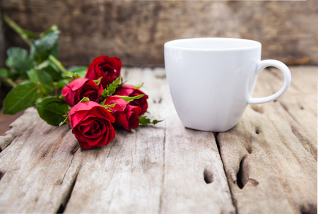 red cup: Bouquet of beautiful red roses and coffee cup for Valentines Day on blurred wooden background. Shallow depth of field (dof), selective focus.
