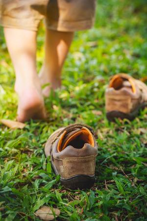 Child take off leather shoes. Child's foot learns to walk on grass, reflexology massage. Kid relax in garden. Shallow depth of field (dof), selective focus.
