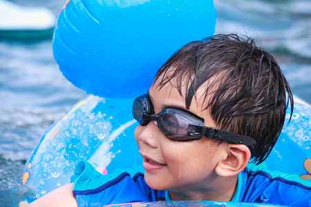 very good: Summer vacation concept - Close up funny asian boy with swim tube in pool. Outdoor. Swimming is very good exercise for good health. Stock Photo