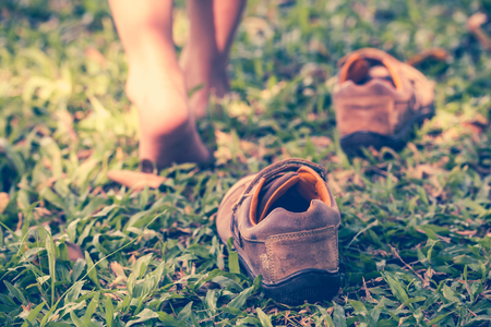 Child take off leather shoes. Close up childs foot learns to walk on grass, reflexology massage. Kid relax in garden. Shallow depth of field (dof), selective focus. Retro style. Фото со стока
