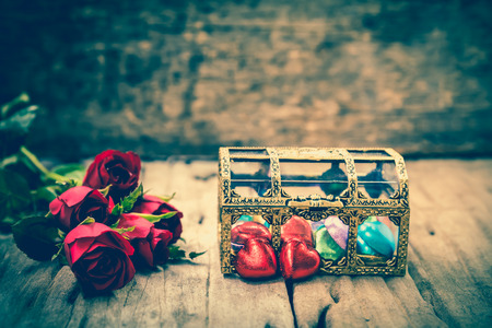 cross process: Bouquet of beautiful red roses and heart-shape of chocolate for Valentines Day on wooden background. Shallow depth of field (dof), selective focus. Vintage picture style. Cross process. Stock Photo