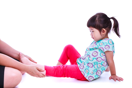 Concept photo of children health and medical care. Caring nurse bandage asian girl's ankle. Mother give first aid at ankle trauma. Studio shot. Isolated on white background. Stock Photo