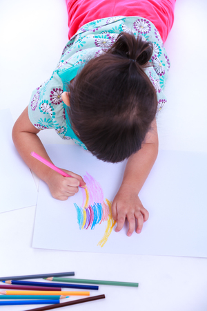strengthen: Top view. Girl lie on the floor and drawing on paper. Concepts of creativity and education, strengthen the imagination of child. Studio shot. On white background.
