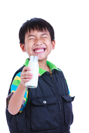 good looking boy: Close up. Fun portrait of handsome asian boy smiling and holding bottle of milk. Drinking milk for good health. Child looking at camera, isolated on white background. Studio shoot. Stock Photo