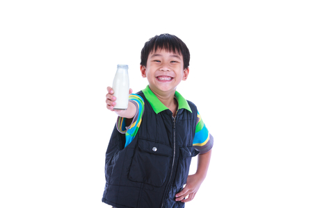 close out: Close up. Fun portrait of handsome asian boy smiling and reach out bottle of milk. Drinking milk for good health. Child looking at camera, isolated on white background. Studio shoot.