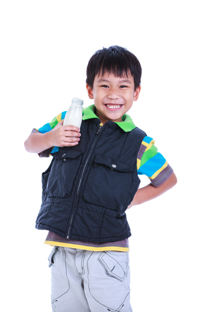 Fun portrait of handsome asian boy smiling and holding bottle of milk. Drinking milk for good health. Child looking at camera, isolated on white background. Studio shoot. Stock Photo