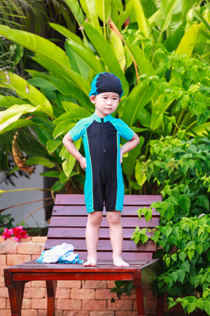 arms akimbo: Cute little asian girl with arms akimbo standing on relaxing chair beside of swimming pool on nature background. Child wearing a colorful swimsuit and bathing cap. Outdoor.