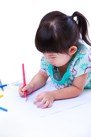 strengthen: Asian girl lie on the floor and drawing on paper. Concepts of creativity and education, strengthen the imagination of child. Studio shot. On white background. Stock Photo