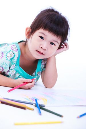 strengthen: Pretty asian girl lie on the floor and looking at camera. Concepts of creativity and education, strengthen the imagination of child. Studio shot. On white background.