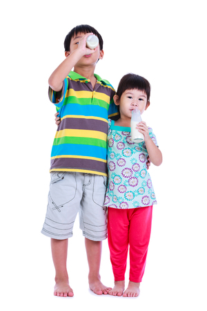 young boy smiling: Fun portrait of children holding bottle of milk. Drinking milk for good health. Two asian boy and girl drinking milk and hugging together, on white background. Studio shoot.