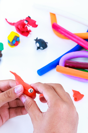 strengthen hand: Child playing and creating toys from clay dough.