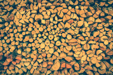 stored: Close up stack of firewood, wood background texture. Layer of stored cut timber. Vintage picture style.
