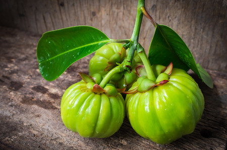 Garcinia atroviridis fresh fruit on old wood background. Herb sour flavor lots of vitamin C for good health. Water drops on leafs. Extract as a weight loss product