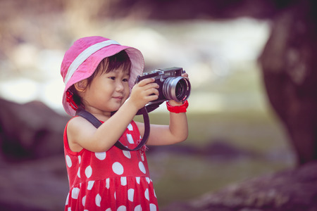 girl portrait: Adorable little asian girl taking photo by professional digital camera on blurred nature background. Pretty child in nature. Outdoors portrait.