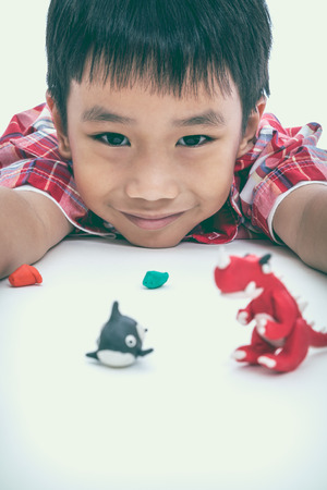 strengthen: Asian handsome child smiling and show his works from clay, on white background. Strengthen the imagination of child. Vintage picture style. Selective Focus. Stock Photo