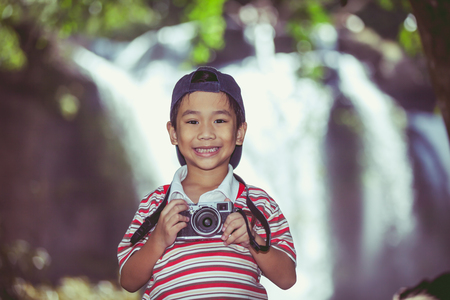 Asian child smiling and holding professional digital camera on blurred waterfall background. Handsome boy in nature. Outdoors portrait. Vintage picture style. Фото со стока