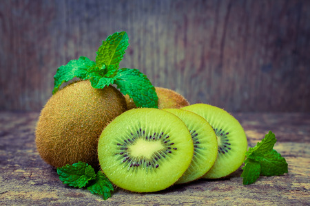 fiber food: Close up fresh kiwi fruit on old wood background. Kiwi fruit is sweet and sour taste, nutritive value and high-fiber. Selective Focus.