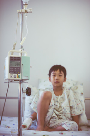 sickbed: Illness asian boy sitting on sickbed in hospital with infusion pump intravenous IV drip. Shallow depth of field (DOF) IV machine in focus, child out of focus. Retro style.