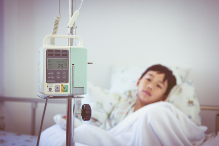 sickbed: Illness asian boy lying on sickbed in hospital with infusion pump intravenous IV drip. Shallow depth of field (DOF) IV machine in focus, child out of focus. Retro style.