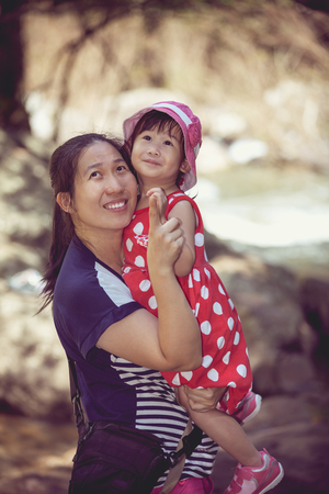30 to 35 years old: Young asian mother and cute little daughter happily on nature background at the day time, mother pointing up. Vintage picture style. Family vacation. Stock Photo