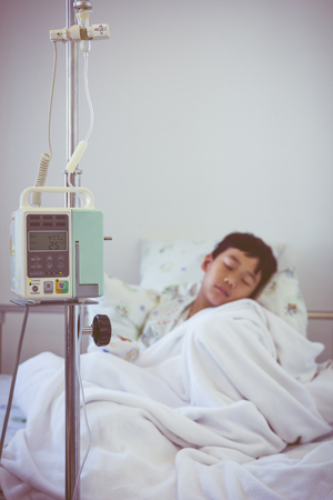 sickbed: Illness asian boy sleeping on sickbed in hospital with infusion pump intravenous IV drip. Shallow depth of field (DOF) IV machine in focus, child out of focus. Retro style. Stock Photo