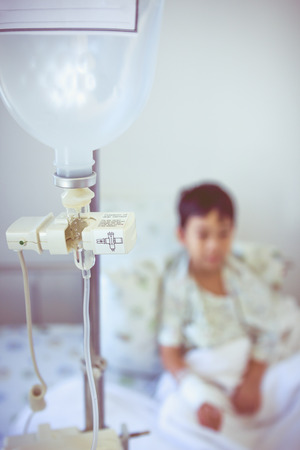 sickbed: Illness asian boy sitting on sickbed in hospital with infusion pump intravenous IV drip. Shallow depth of field (DOF) drop in intravenous (IV) drip in focus, child out of focus. Retro style.