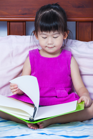preschoolers: A little cute asian girl in a purple dress reading a book sitting on bed in bedroom. Preschoolers learn and study at home, education concept. Kids learning. Stock Photo