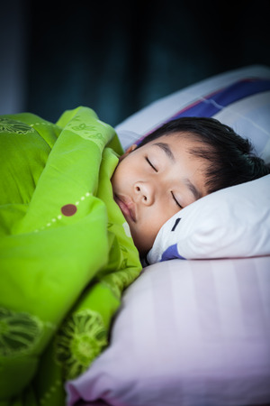 peacefully: Healthy child. Little asian boy sleeping peacefully on bed in dark bedroom. Vignette picture style.