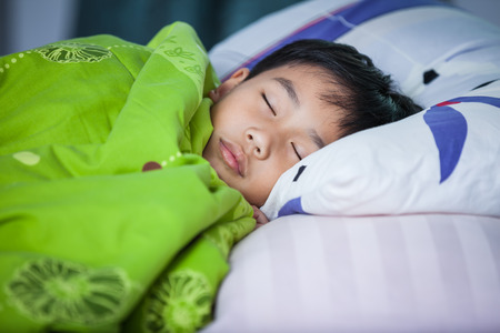 Healthy child. Little asian boy sleeping peacefully on bed in dark bedroom.