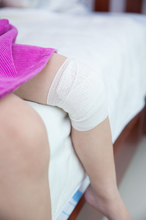 injurious: Child injured. Wound on the childs knee with bandage. Shallow depth of field (DOF), selective focus, bandage in focus. Human health care and medicine concept.