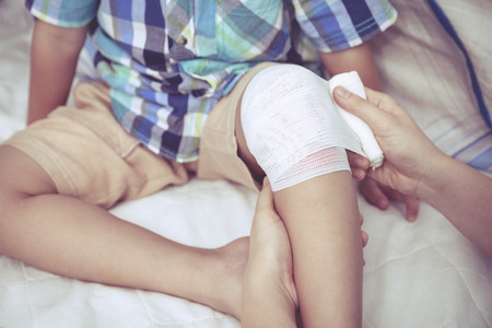 knee: Child injured. Mother bandaging sons knee. Human health care and medicine concept.