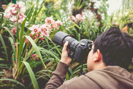 orchid house: Back view of asian male photographer taking photo beautiful orchid flowers in a orchid house by digital camera on blurred nature background. Vintage picture style. Stock Photo