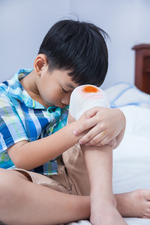 injurious: Child injured on bed in bedroom. Bloody wound on the childs knee with bandage. Sad boy. Human health care and medicine concept. Stock Photo