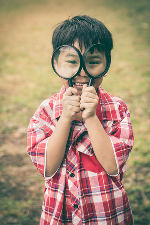 peers: Playful  asian child enjoying in nature. Young handsome boy peers at the camera through two magnifying glass on blurred nature background. Outdoors in the day time. Vintage style.